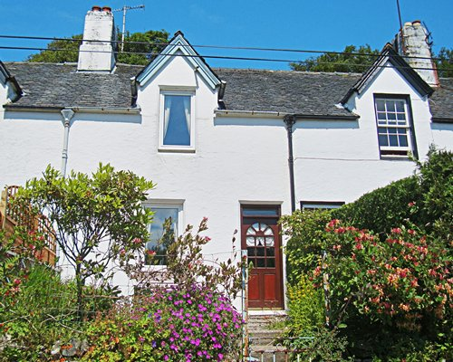 An exterior view of the cottage with flowering shrubs.
