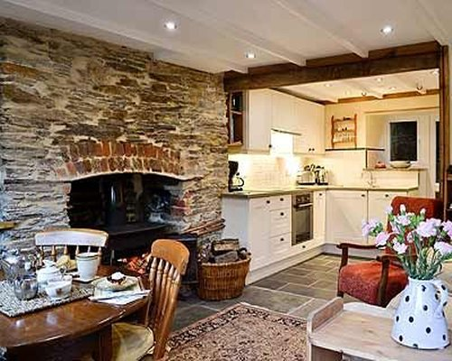 An open plan kitchen and dining area with a fireplace.