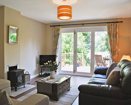 A well furnished living room with television fireplace and patio furniture in the balcony.