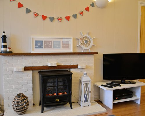 A living room with a television and fire at the fireplace.