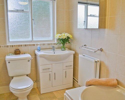A bathroom with bathtub and closed sink vanity.