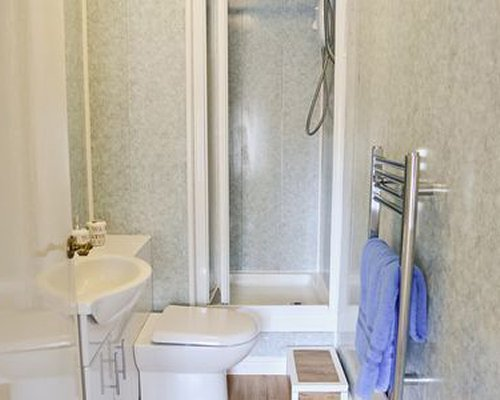 A bathroom with shower shower stall and a sink.