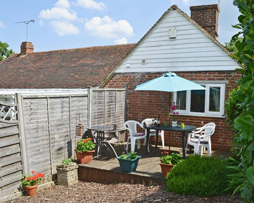 Scenic view of a unit at Beechurst Cottage with patio chairs and sunshade.