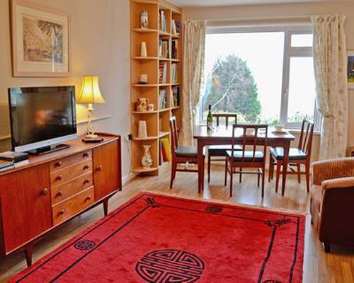 A well furnished living room with television dining area bookshelf and outside view.