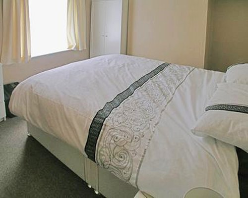 A well furnished bedroom with double bed and outside view.