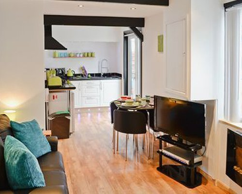 A well furnished living room with a television and open plan kitchen with dining area.