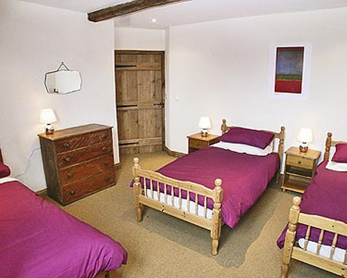 A well furnished bedroom with three beds.