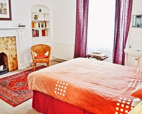 A well furnished bedroom with fireplace and vanity.