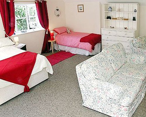 A well furnished bedroom with two beds and living area.