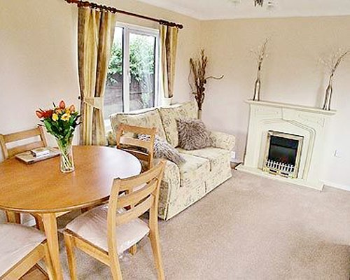 A well furnished living and dining area with a fireplace and an outside view.