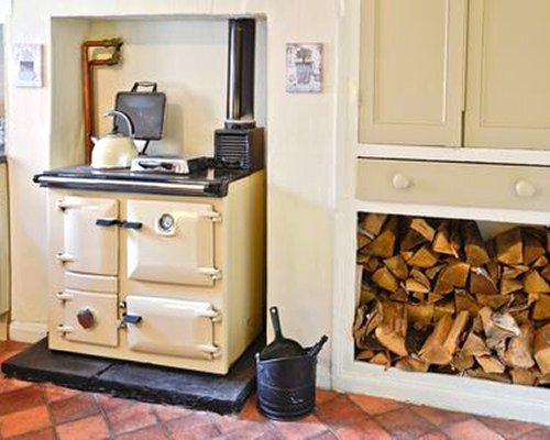 A well equipped kitchen with a wood burning stove.