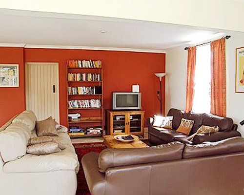 A well furnished living room with a television bookshelf and outside view.