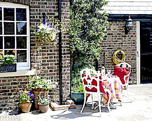 Outdoor dining alongside a unit at Sutton Cottage.