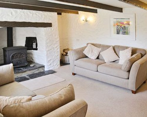 A well furnished living room with a fireplace and double pull out sofa.