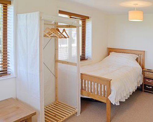 A well furnished bedroom with cloth dryer stand.