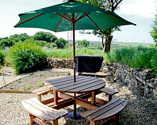 Outdoor picnic area with sunshade and barbecue grill.
