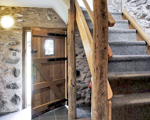 A wooden cottage door and carpeted staircase.