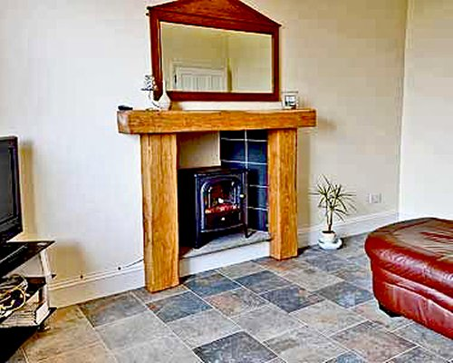 A well furnished room with a television and fireplace.