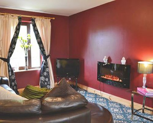 A well furnished living room with a television fire in the fireplace and outside view.