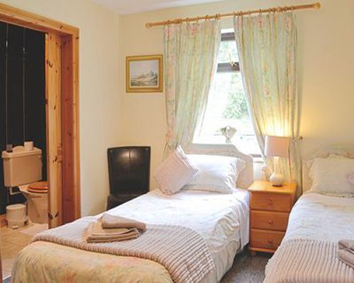 A well furnished bedroom wit two twin beds television outside view and bathroom.