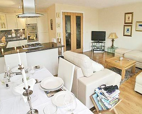 A well furnished living room with a sofa dining table television and open plan kitchen.