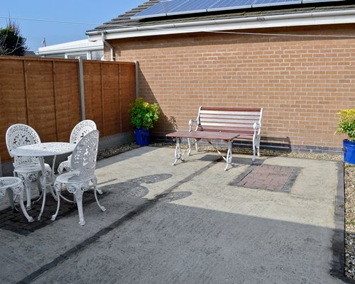 Outdoor picnic area with dining wooden bench and landscaping alongside a unit.
