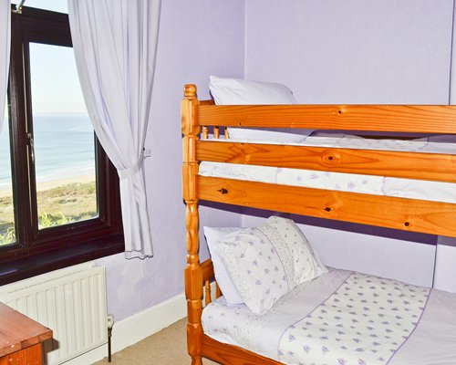 A well furnished bedroom with bunk beds and beach view.