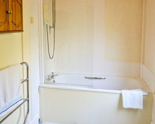 A bathroom with bathtub and shower.