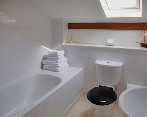 A bathroom with bathtub shower and single sink.