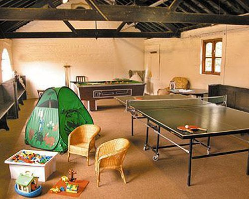 An indoor recreational area with pool table and ping pong table.