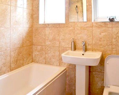 A bathroom with a bathtub and single sink vanity.