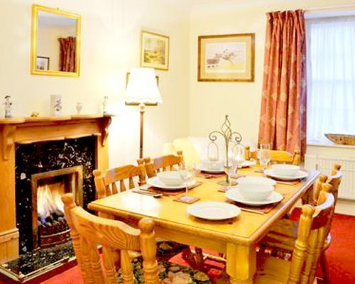 A well furnished dining room with a fire in the fireplace.