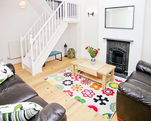 A well furnished living room with fireplace alongside a stairway.