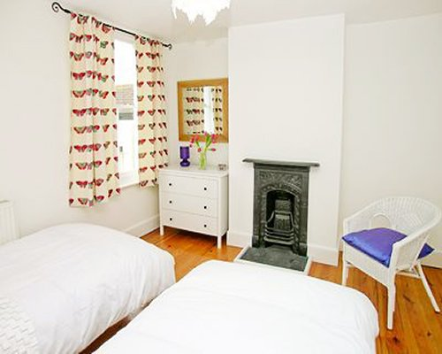 A well furnished bedroom with two twin beds and a fireplace.