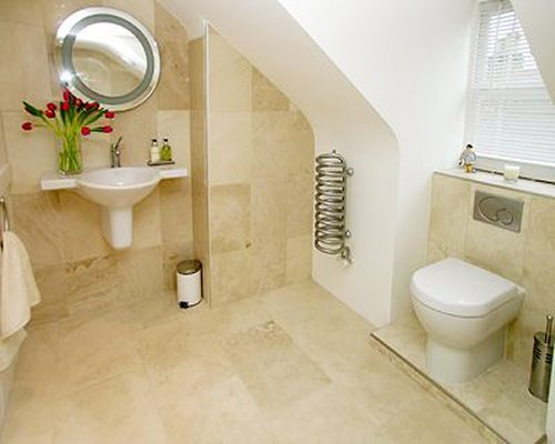 A bathroom with open sink vanity and toilet.