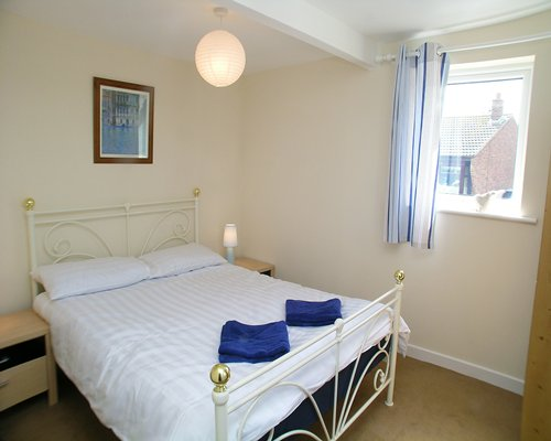 A well furnished bedroom with a double bed and an outside view.