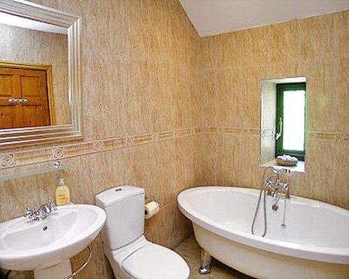 A bathroom with bathtub shower and single sink vanity.