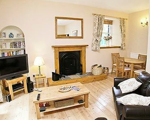A well furnished living room with a television fireplace and dining table.