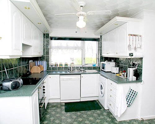 A well equipped kitchen with a microwave oven and an outside view.
