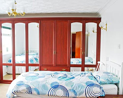 A well furnished bedroom with two twin beds and mirrored wardrobe.
