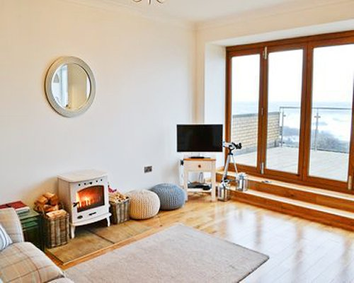 A well furnished living room with a television fire in the fireplace balcony and beach view.