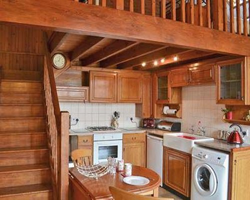 An open plan kitchen with dining area and wooden staircase.