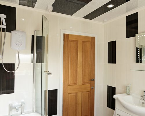 A bathroom with a single sink vanity and shower.
