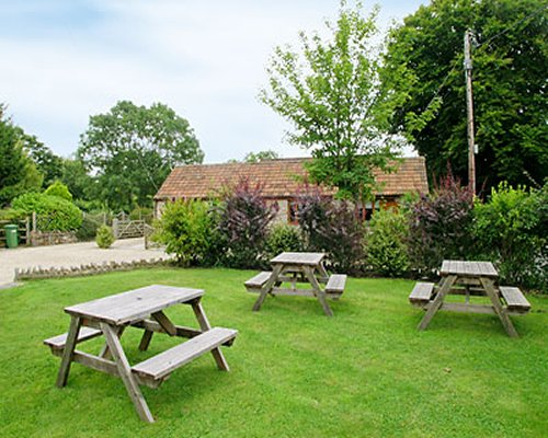 View of picnic seats in a well maintained lawn alongside the cottage.