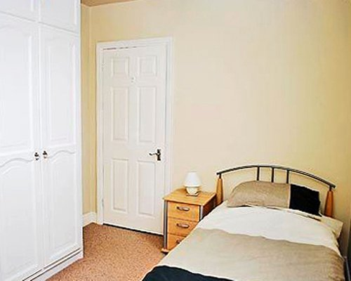 A well furnished bedroom with a twin bed.