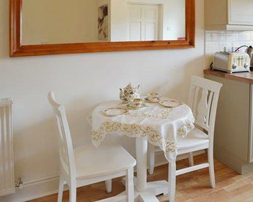 Furnished dining room alongside a kitchen.