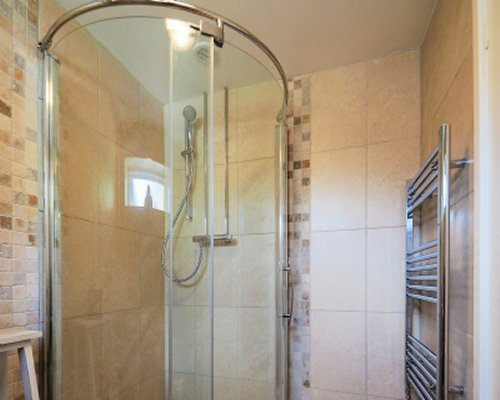 A bathroom with shower stall and wall towel warmer.