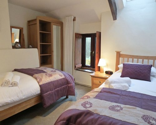 A furnished bedroom with twin beds and a window.