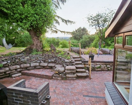 A landscaped back patio with stone walls and grill.