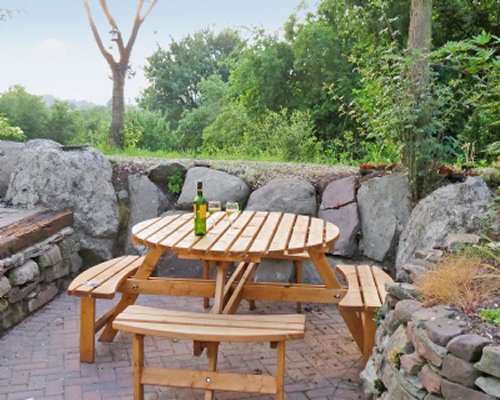 A round picnic table on patio with stone walls.